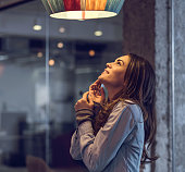 Young happy woman standing and looking at lamp.
