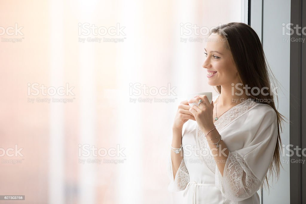 Young happy woman standing near the window stock photo