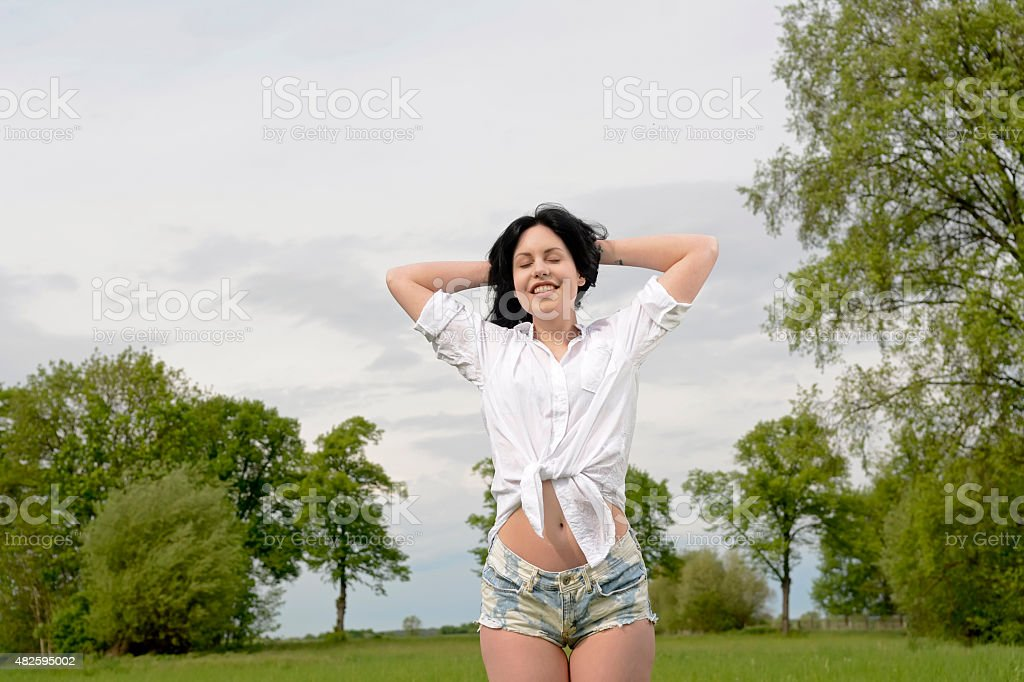 Young happy woman standing on meadow stock photo