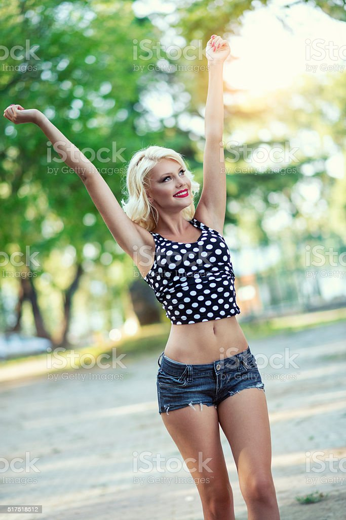 Young Happy Woman Walking with Spread Arms in City Park stock photo