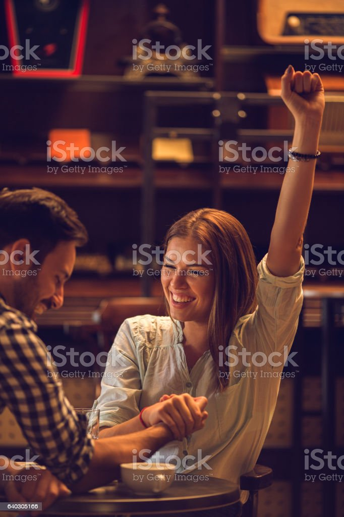 Young happy woman winning in arm wrestling with boyfriend. stock photo