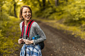 Young happy woman with backpack laughing in the forest.