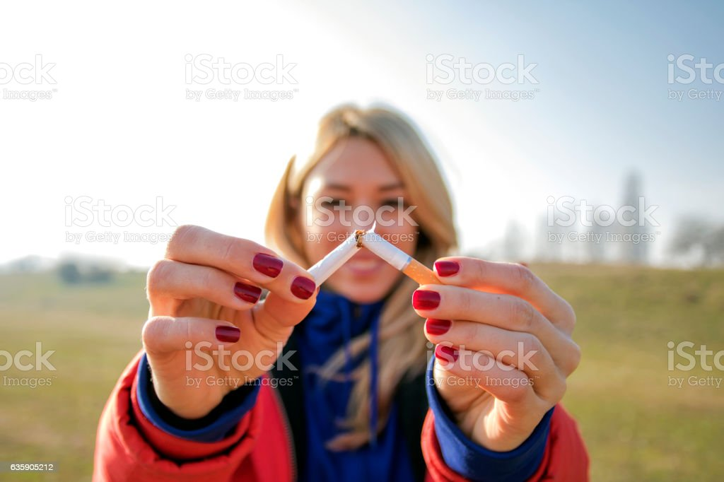 Young happy woman with broken cigarette. Stop smoking concept. stock photo