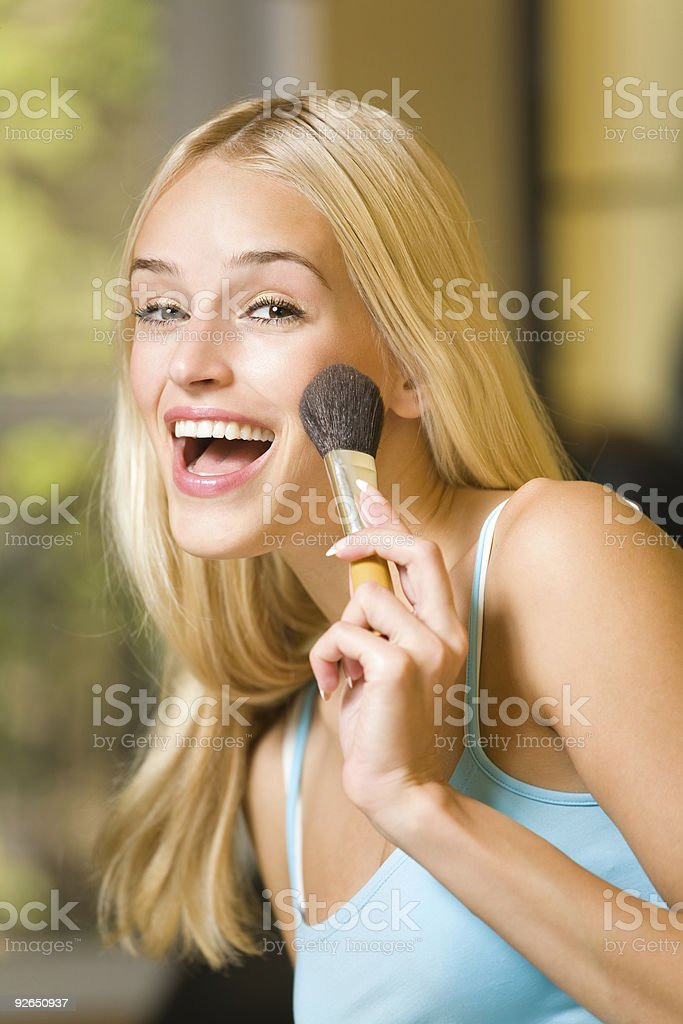 Young happy woman with makeup brush indoors royalty-free stock photo