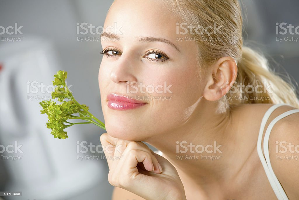Young happy woman with parsley at kitchen royalty-free stock photo