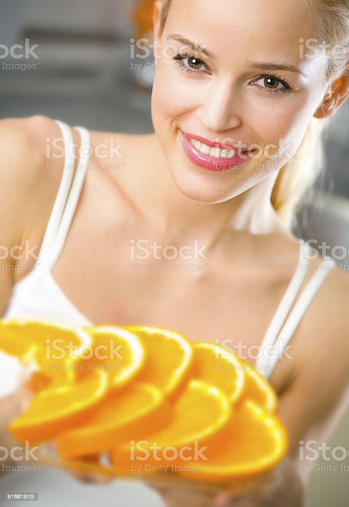 Young happy woman with plate of orange royalty-free stock photo