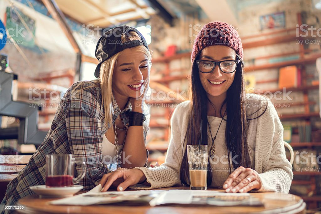 Young happy women relaxing in a cafe and reading magazine. stock photo