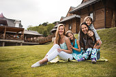 Young happy women relaxing on grass with their kids.