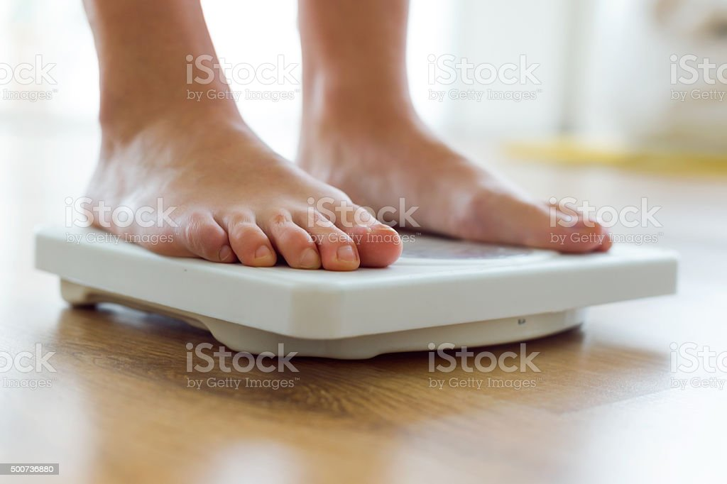 Young healthy girl on home scales. stock photo