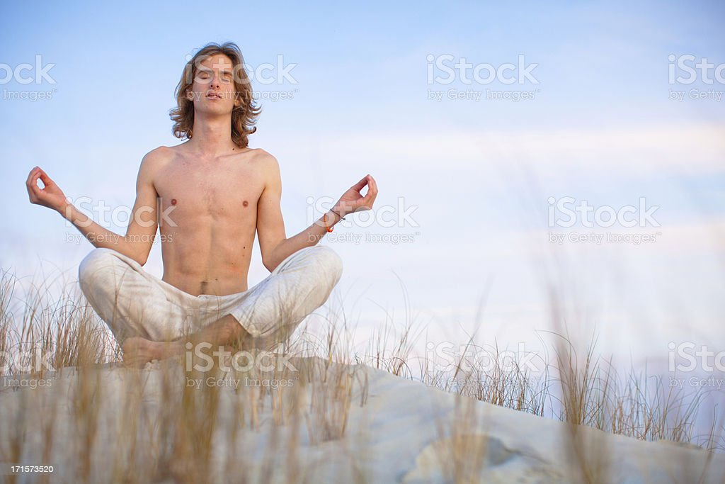 Young healthy man meditating on the beach royalty-free stock photo