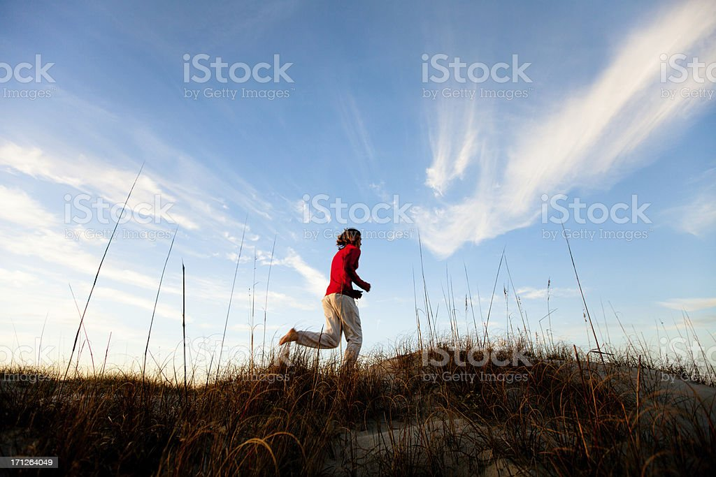 Young healthy man running barefoot on the beach stock photo