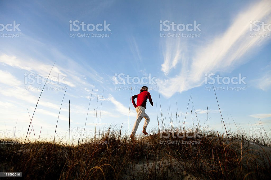 Young healthy man running barefoot on the beach royalty-free stock photo