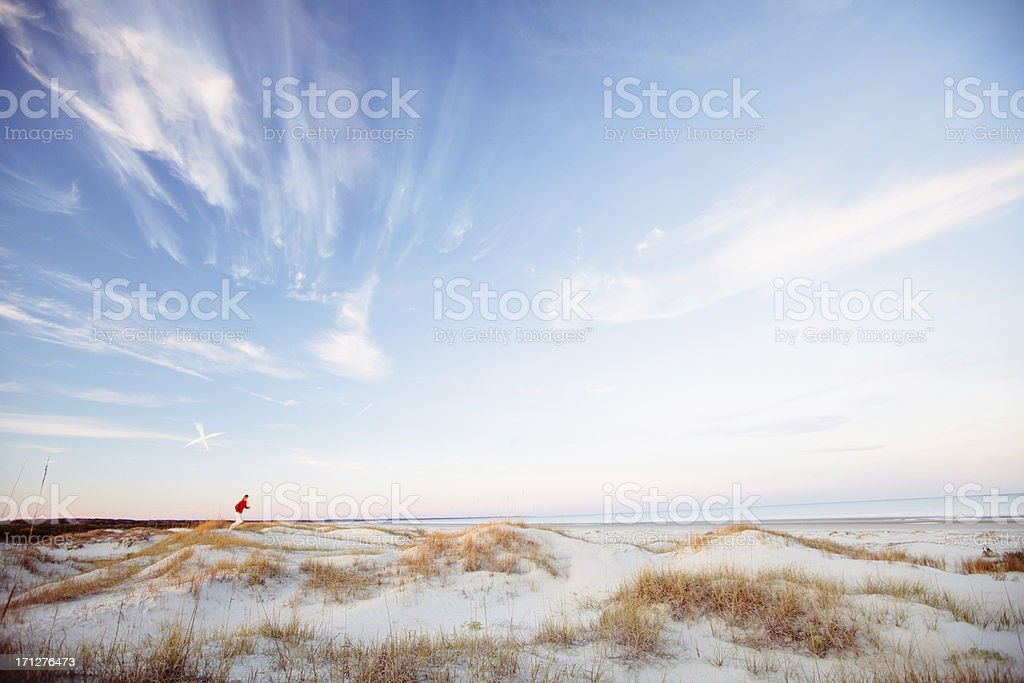 Young healthy man running on the beach at sunset stock photo