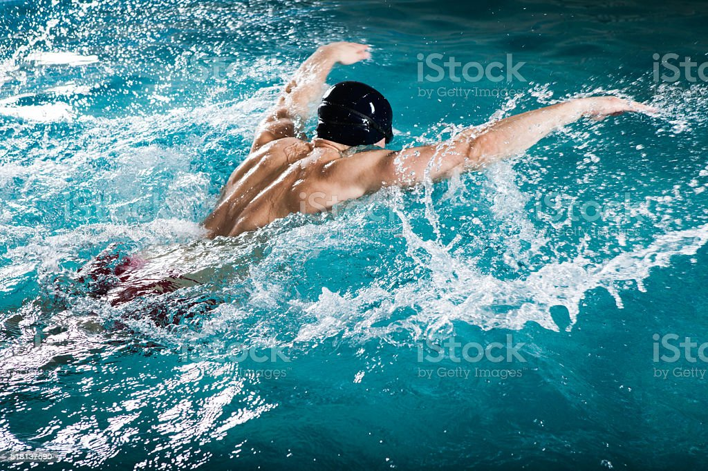 Young healthy man with muscular body swims stock photo