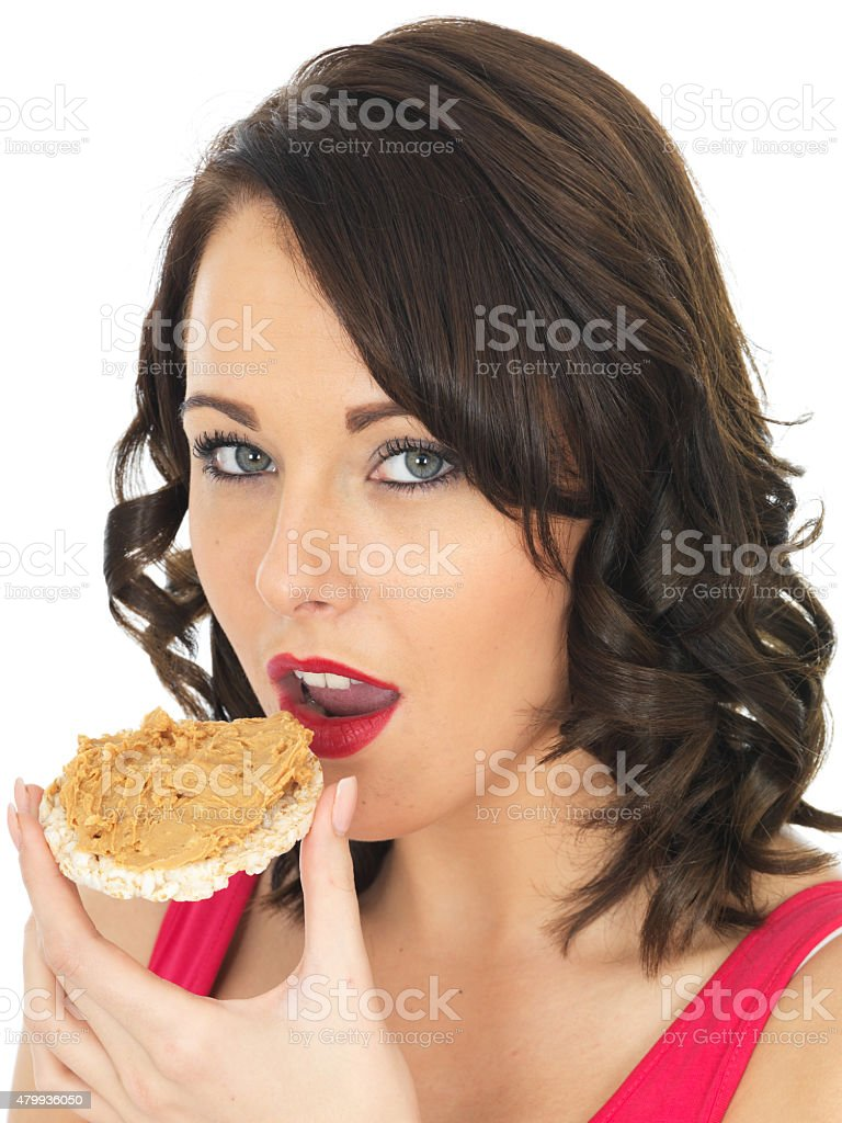 Young Healthy Woman Eating Peanut Butter on a Cracker stock photo
