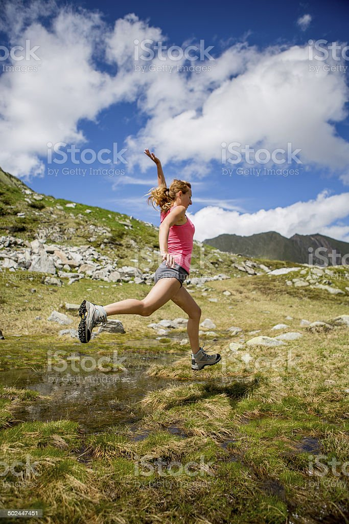 Young healthy woman in sport clothing jumping through grass stock photo