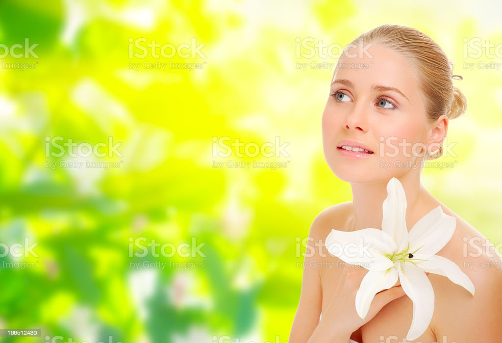 Young healthy woman with flower on spring background royalty-free stock photo