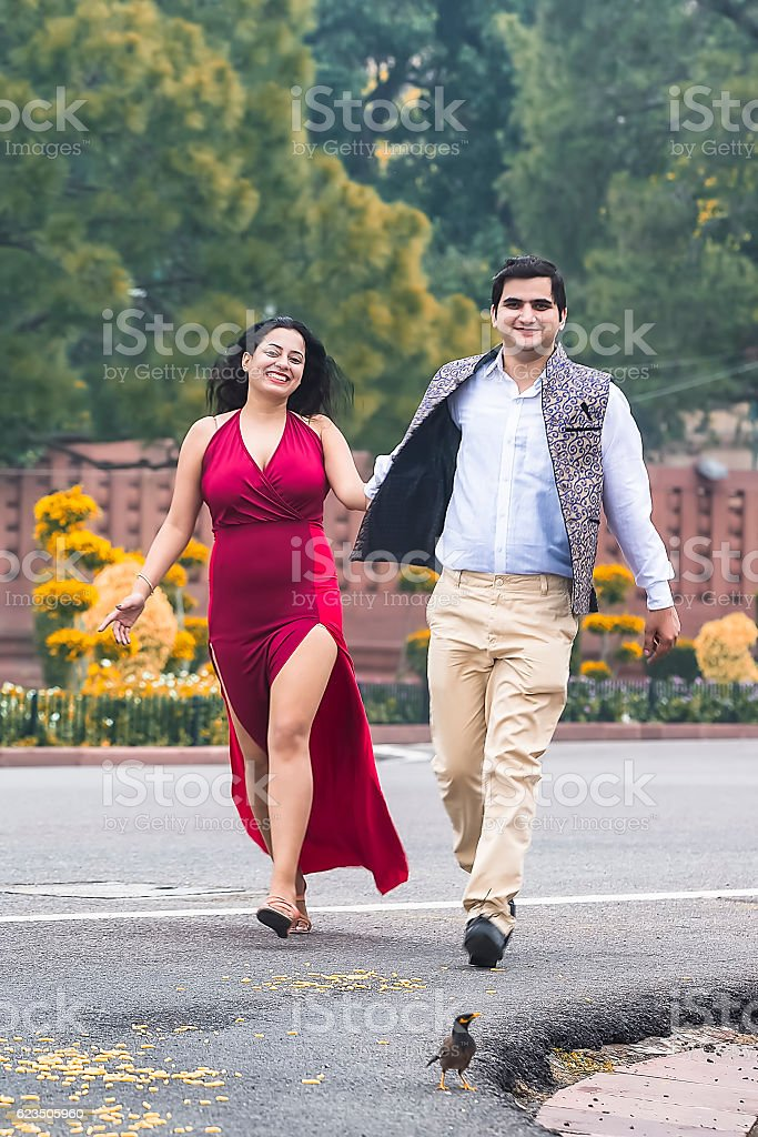 Young heterosexual couple, running on the road holding their hands stock photo