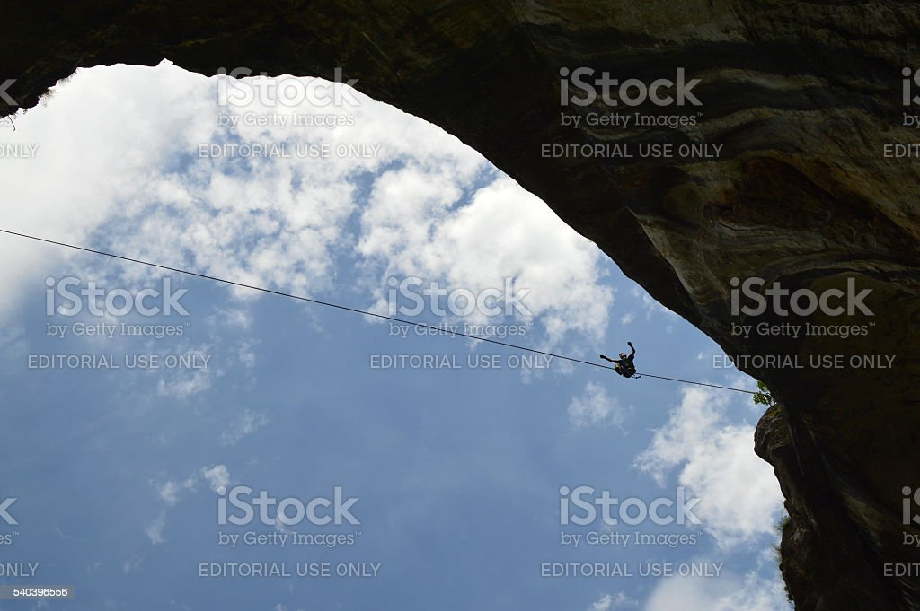 Young highline walker high on tightrope in the sky stock photo