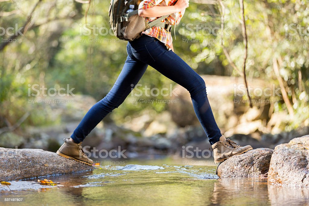 young hiker crossing stream in mountain stock photo