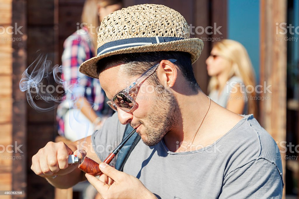 young hiker lights his pipe in front of the hut stock photo