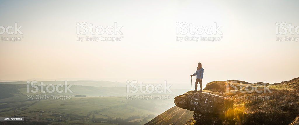 Young hiker looking out over mountain valley misty dawn panorama stock photo
