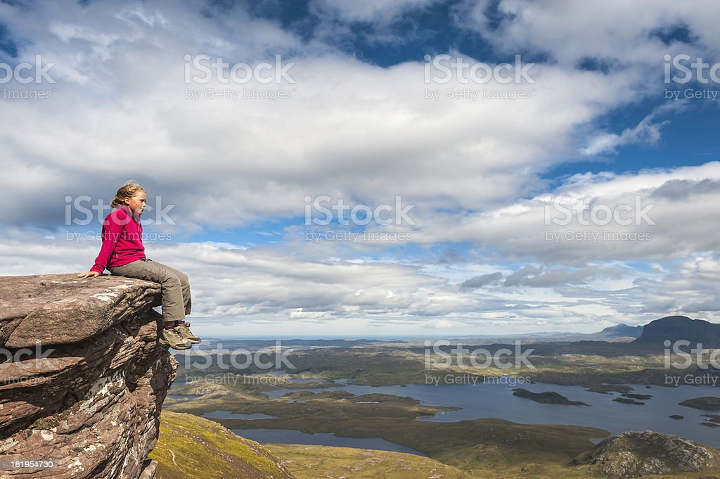 Young hiker looking over wilderness from mountain summit stock photo