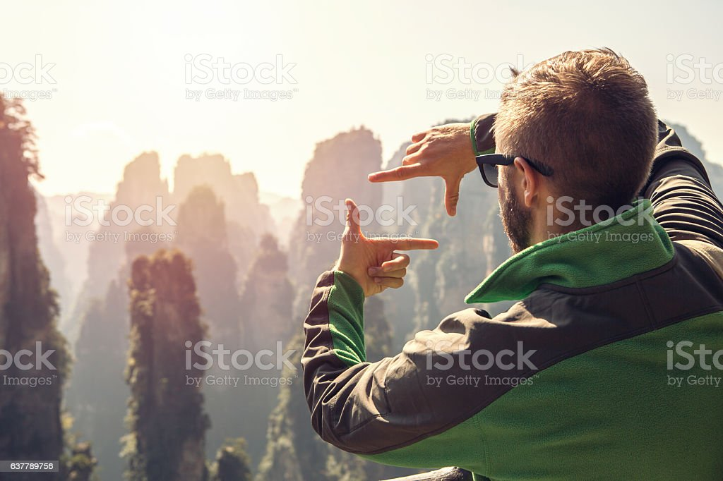 Young hiker male framing landscape with fingers stock photo