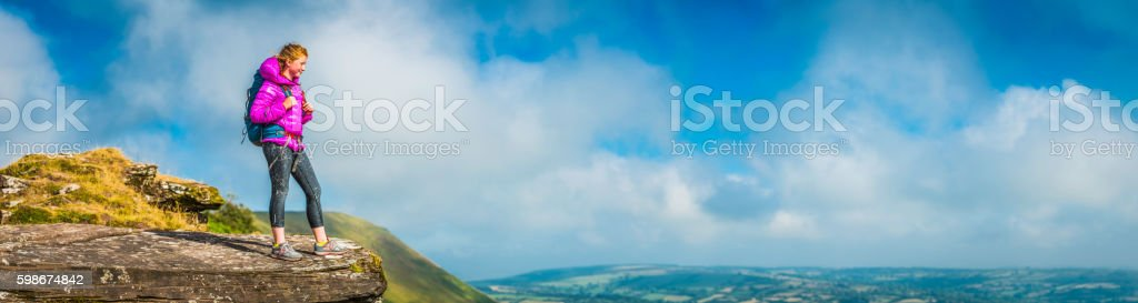 Young hiker on green mountain ridge overlooking panoramic rural view stock photo