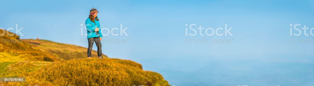 Young hiker on mountain ridge overlooking blue valley vista panorama stock photo