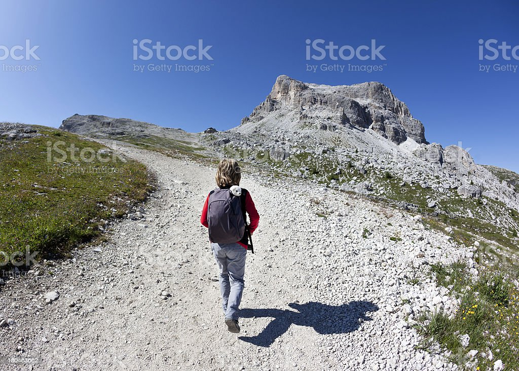 Young hiker walking on a mountain trail. stock photo