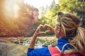 Young hiker woman framing landscape in heart frame