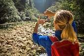 Young hiker woman framing landscape in natural frame