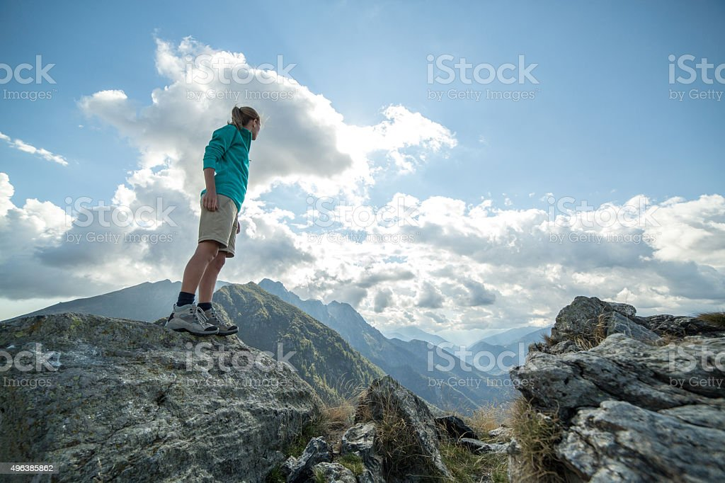Young hiker woman standing on mountain top admiring the landscape stock photo