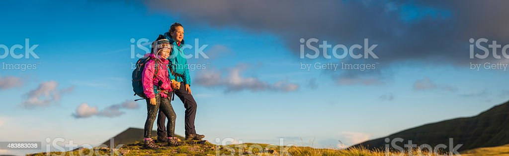 Young hikers looking at sunset from mountain top wilderness panorama stock photo