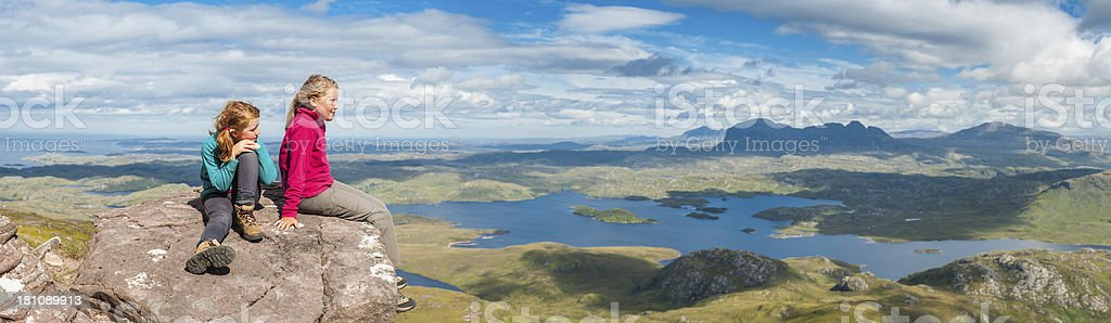 Young hikers looking out over dramatic mountain wilderness panor stock photo