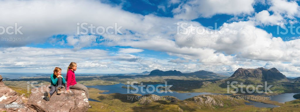 Young hikers looking over mountain wilderness panorama stock photo