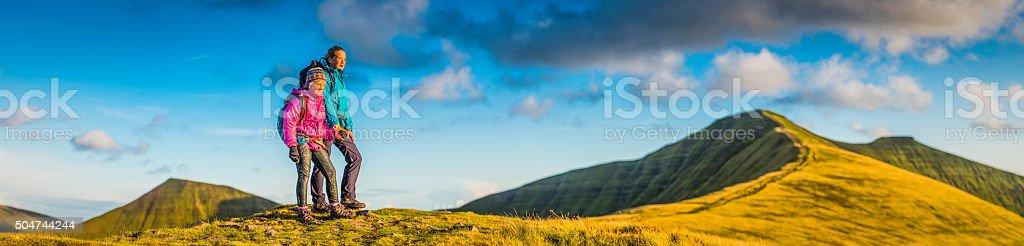 Young hikers on green mountain ridge watching wilderness sunset panorama stock photo