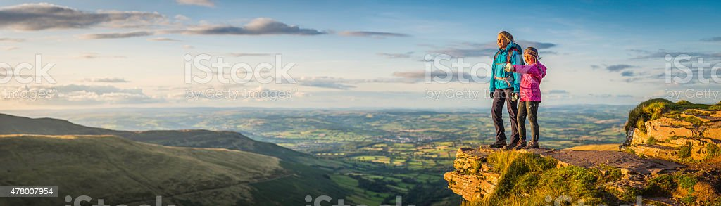 Young hikers on mountain top overlooking idyllic sunset landscape panorama stock photo