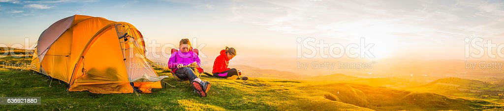 Young hikers relaxing on idyllic summer sunset mountain tent camp stock photo
