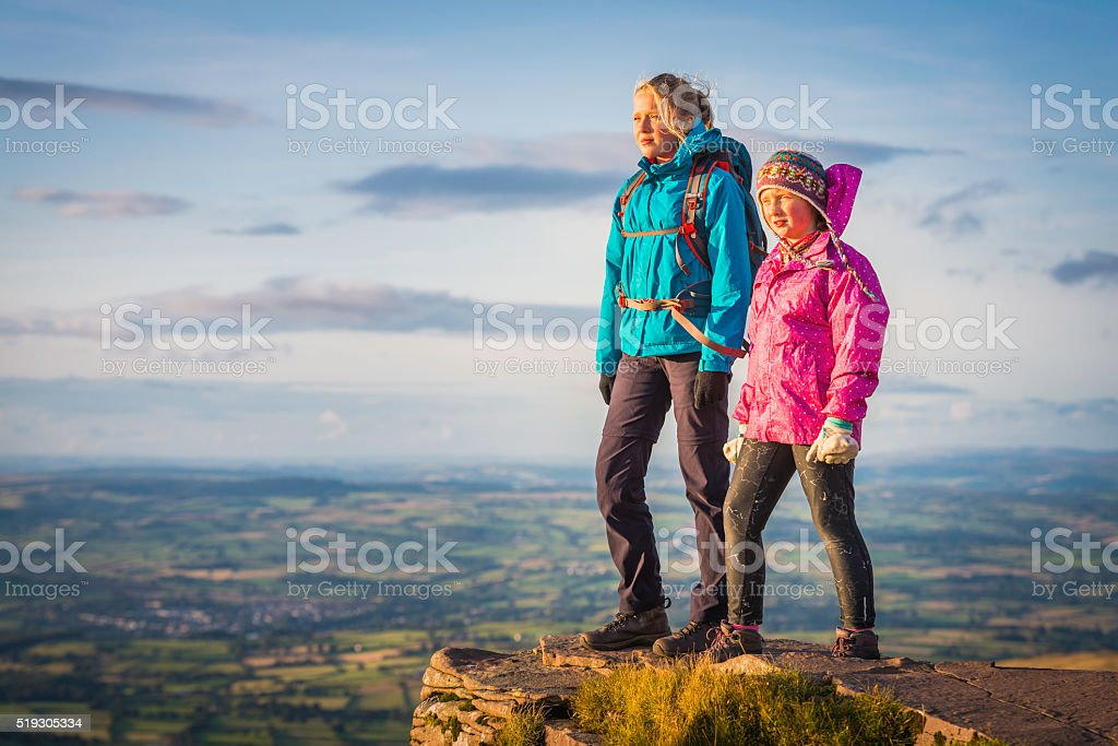 Young hikers standing on mountain top looking out at view stock photo