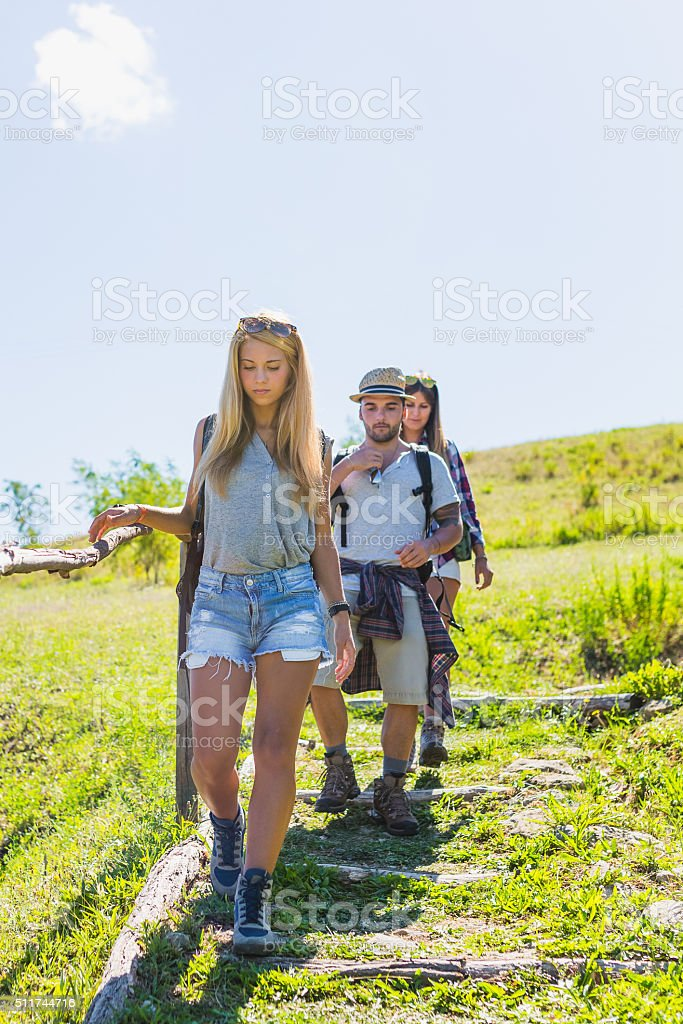 Young hikers walking on mountain trail stock photo