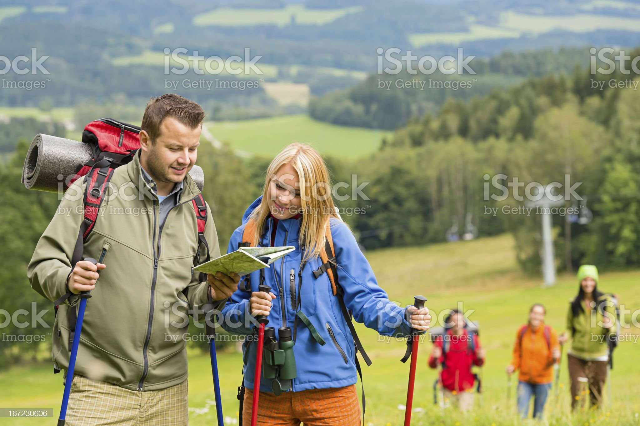 Young hiking friends reading map find track royalty-free stock photo