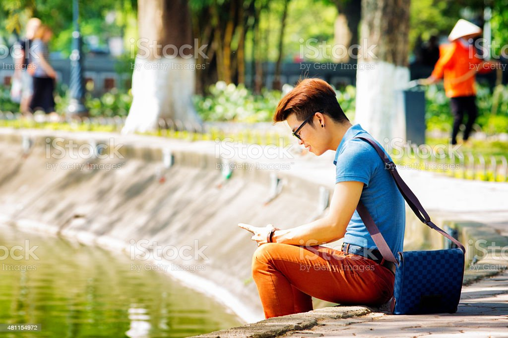 Young hip Vietnamese male student text messaging in park stock photo