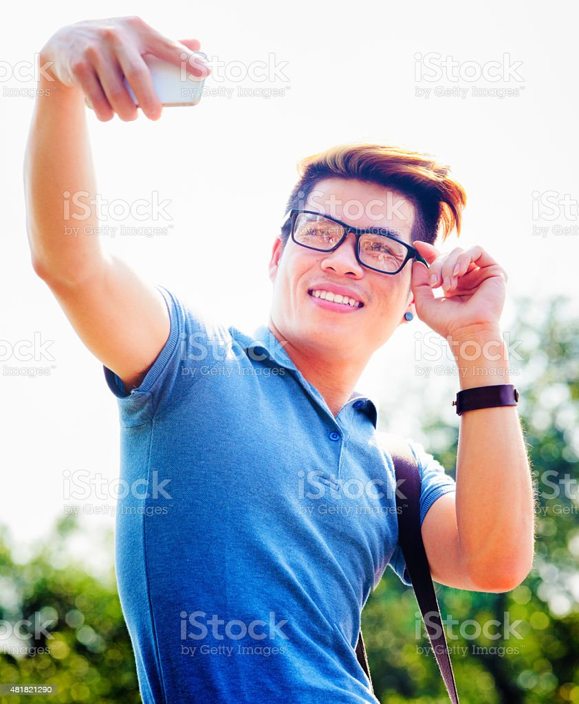 Young hip Vietnamese male tourist shoots selfie adjusting glasses stock photo