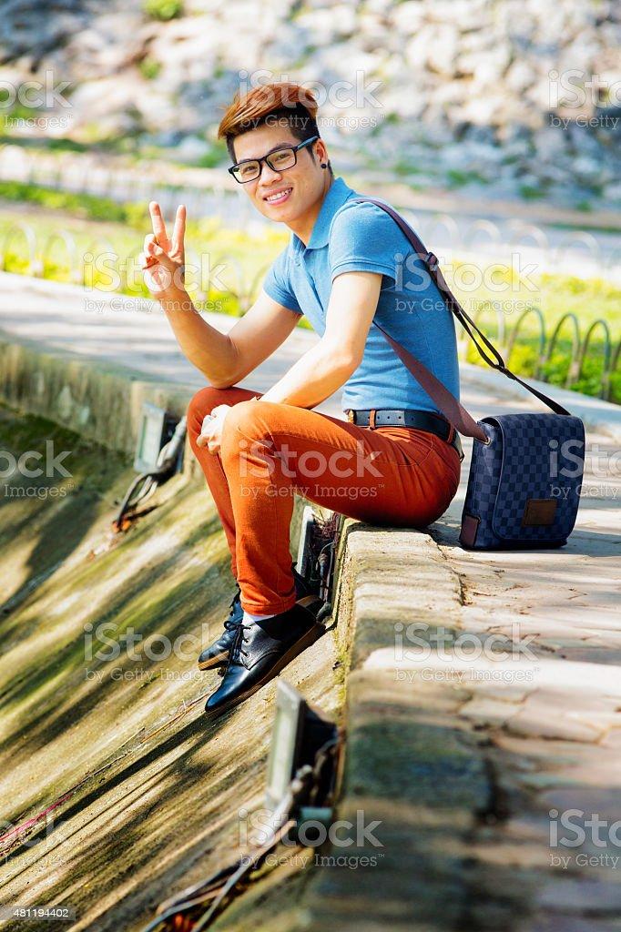 Young hip Vietnamese man at Hoan Kiem lake peace sign stock photo