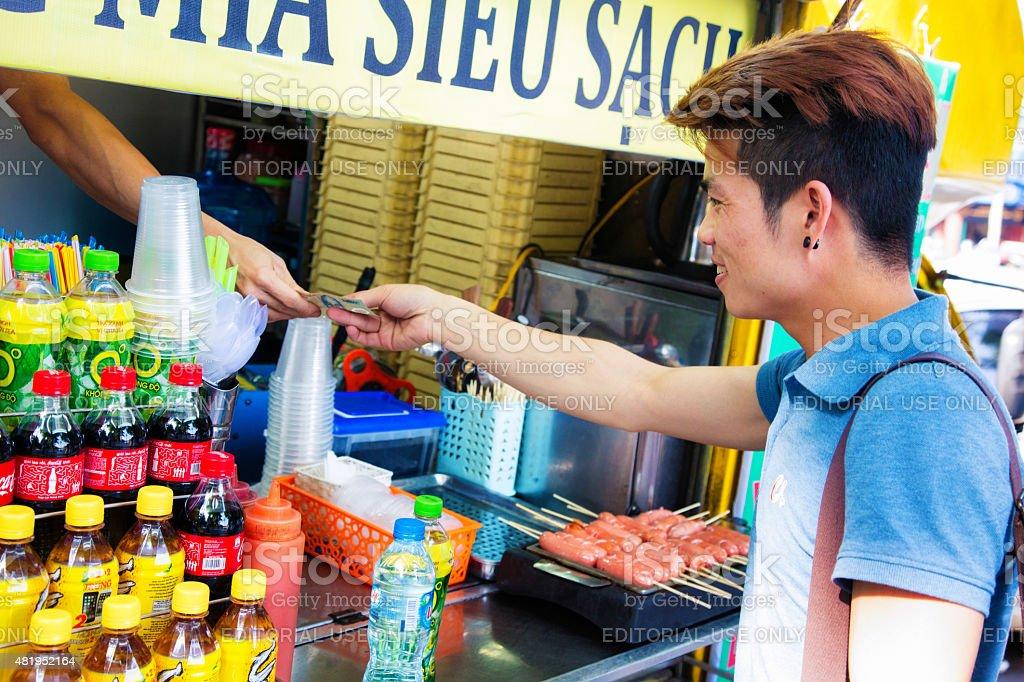 Young hip Vietnamese man buying water bottle street stand Hanoi stock photo