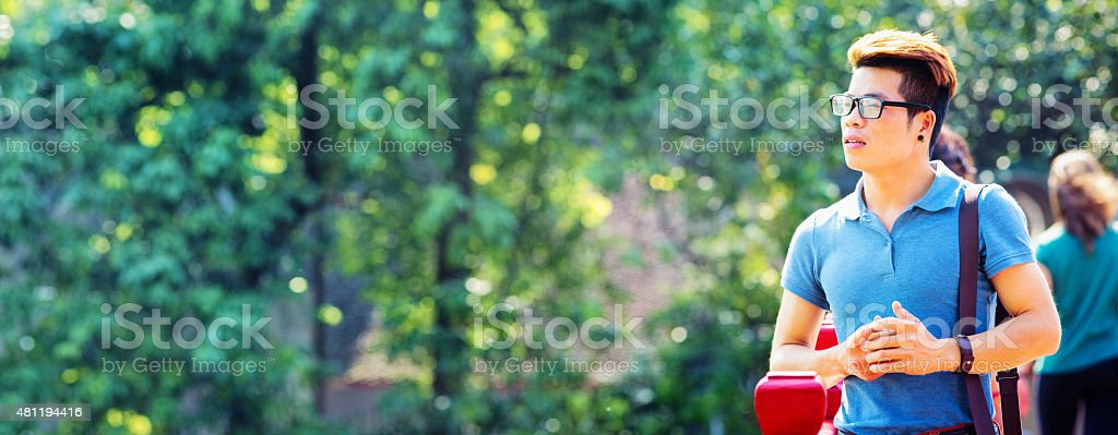 Young hip Vietnamese man pensive in park panorama stock photo