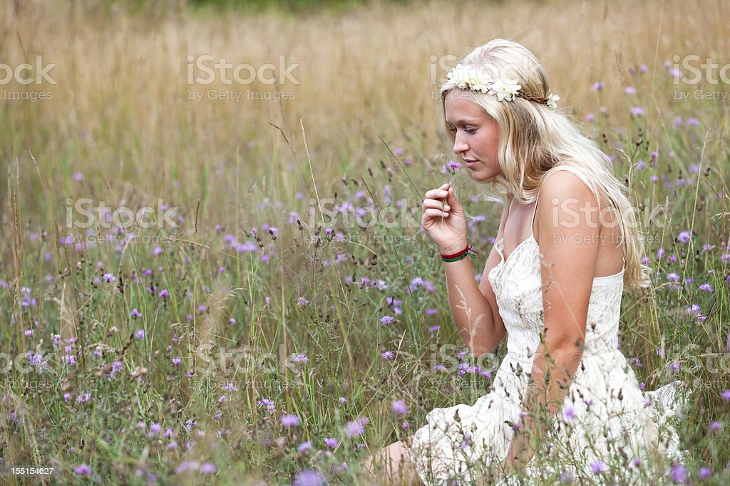young hippie girl smelling nature field flower stock photo
