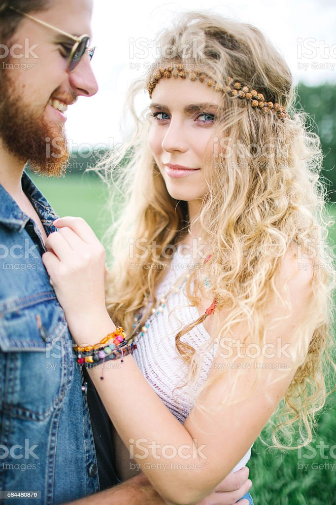 Young hippie male with beard hugging curly female outdoors stock photo
